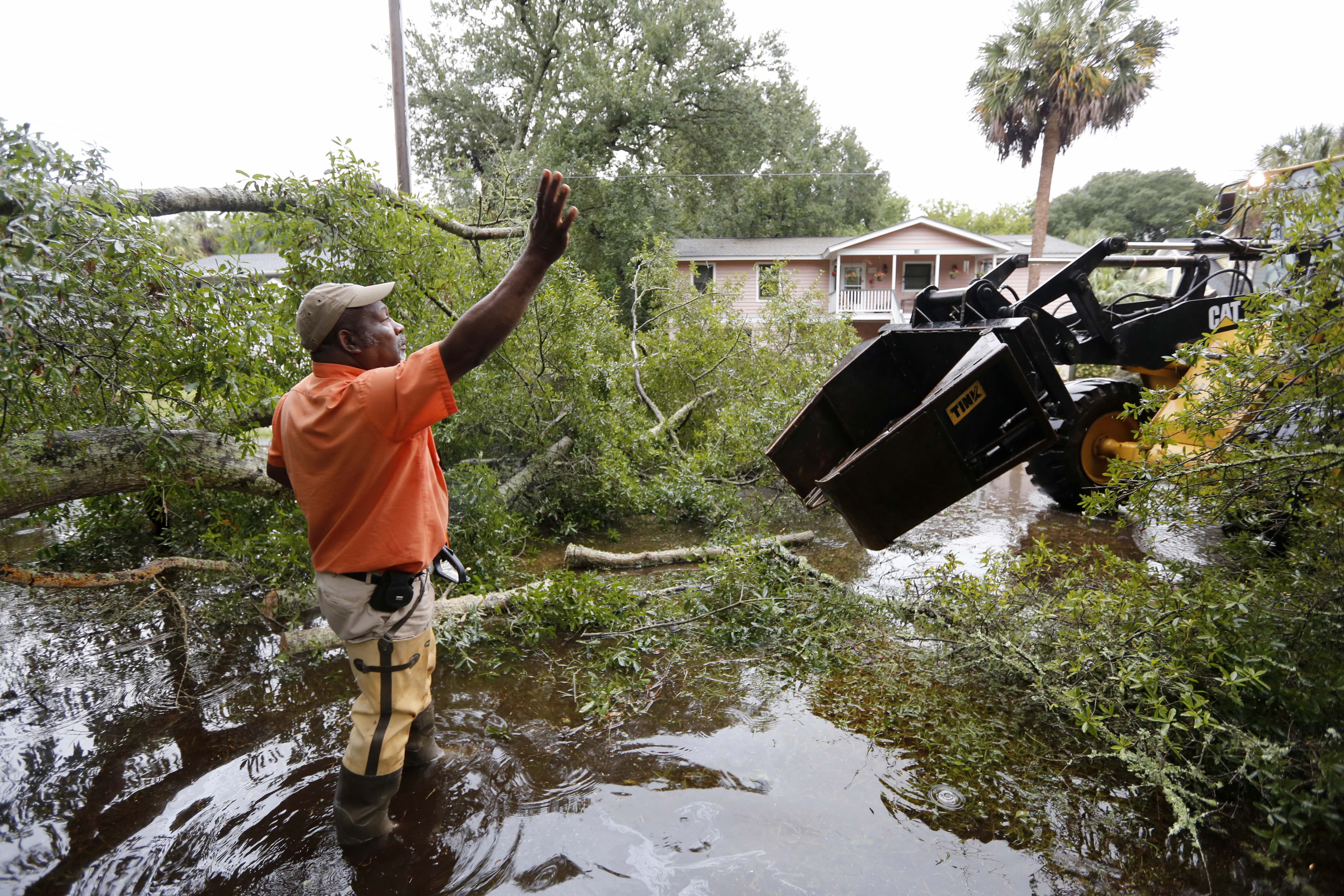 George Myers with the city of Isle of Palms directs equipment in on 23rd Ave. to clear the road after heavy rains fell on the Isle of Palms, S.C., Sunday, Oct. 4, 2015