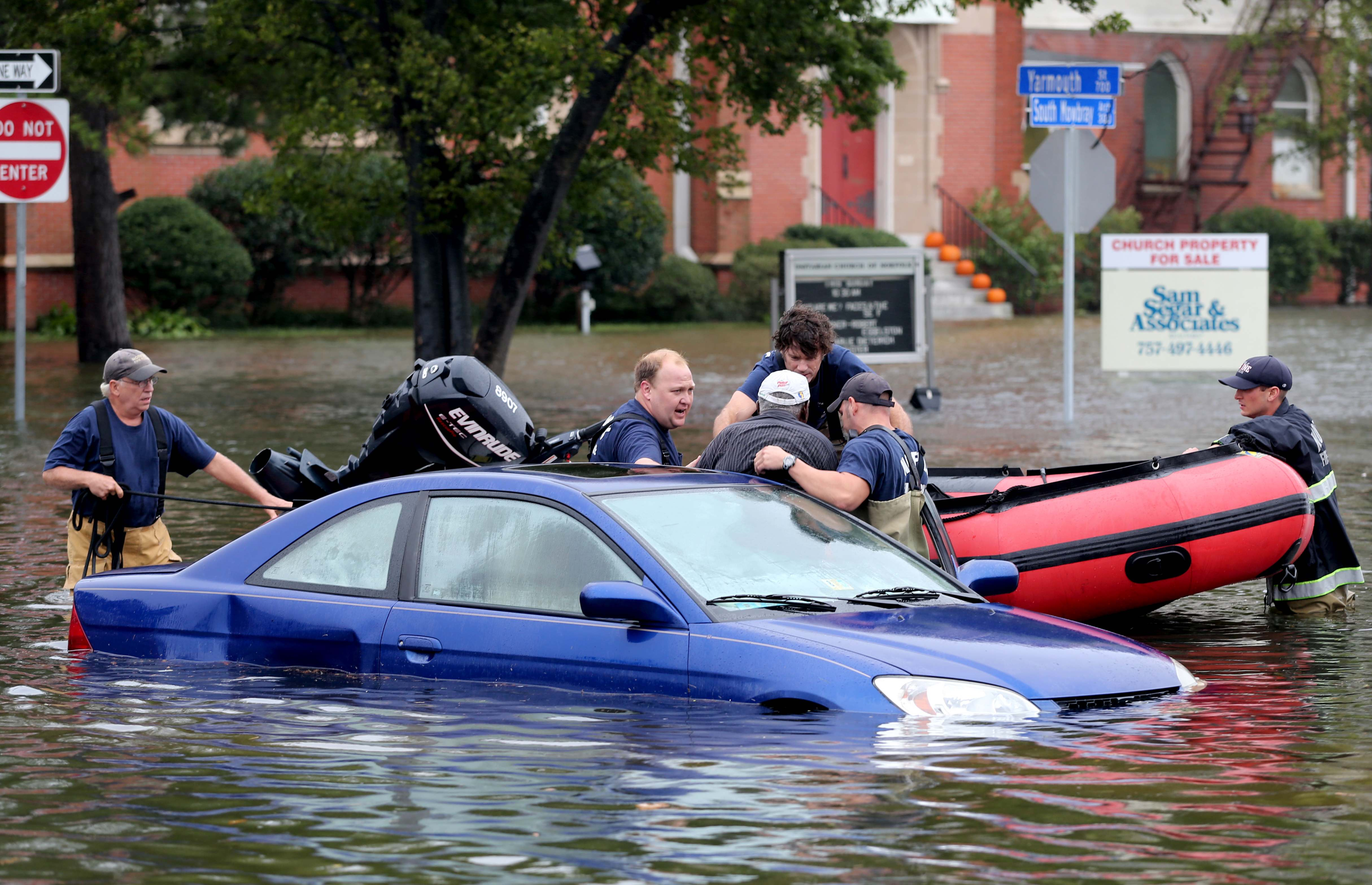 Members of Norfolk Fire-Rescue pull a man from his car stranded because of flooding in Norfolk, Va., on Sunday, Oct. 4, 2015.