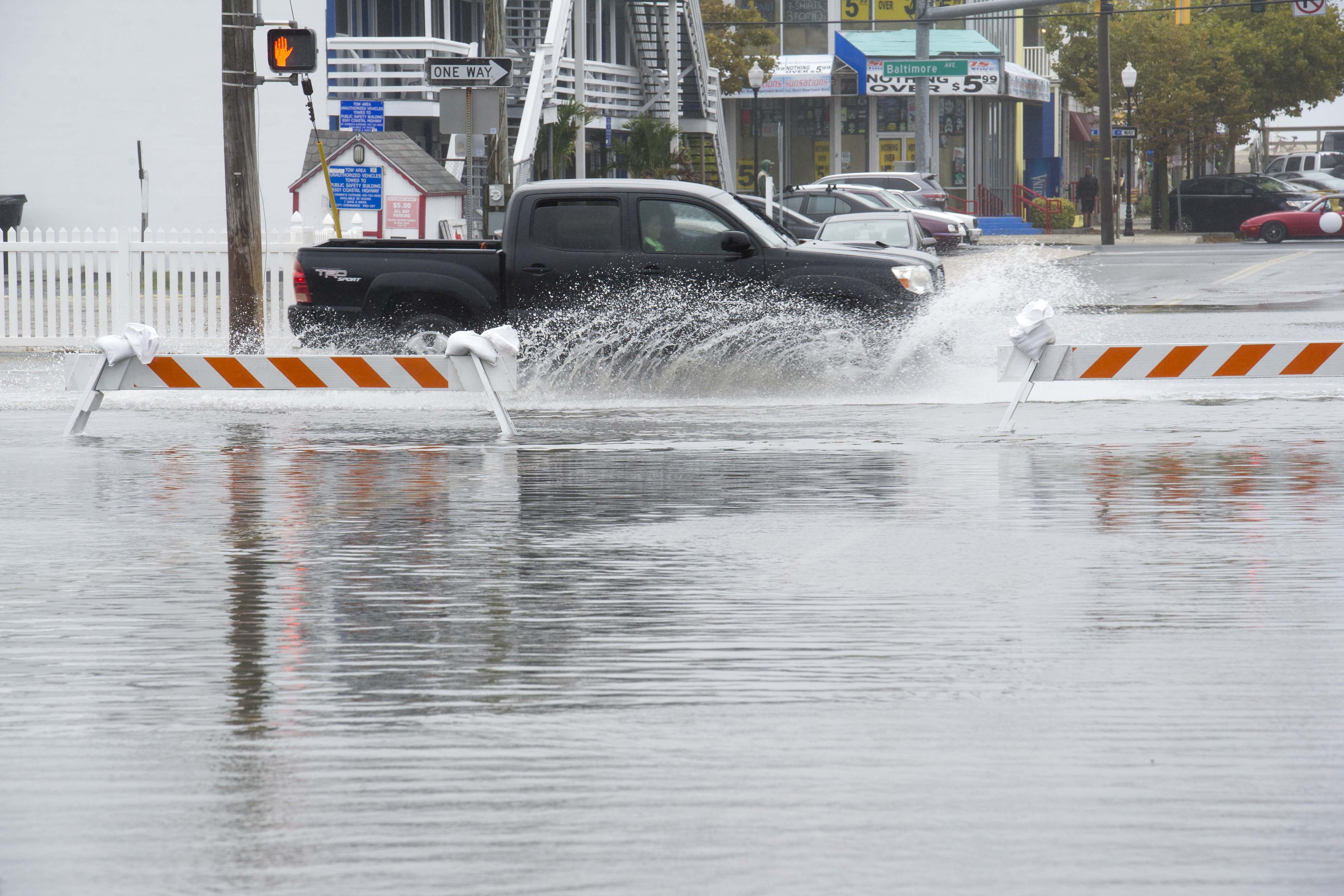 Traffic drives on flooded roads, at high-tide, in downtown Ocean City, Md., Saturday, Oct. 3, 2015.