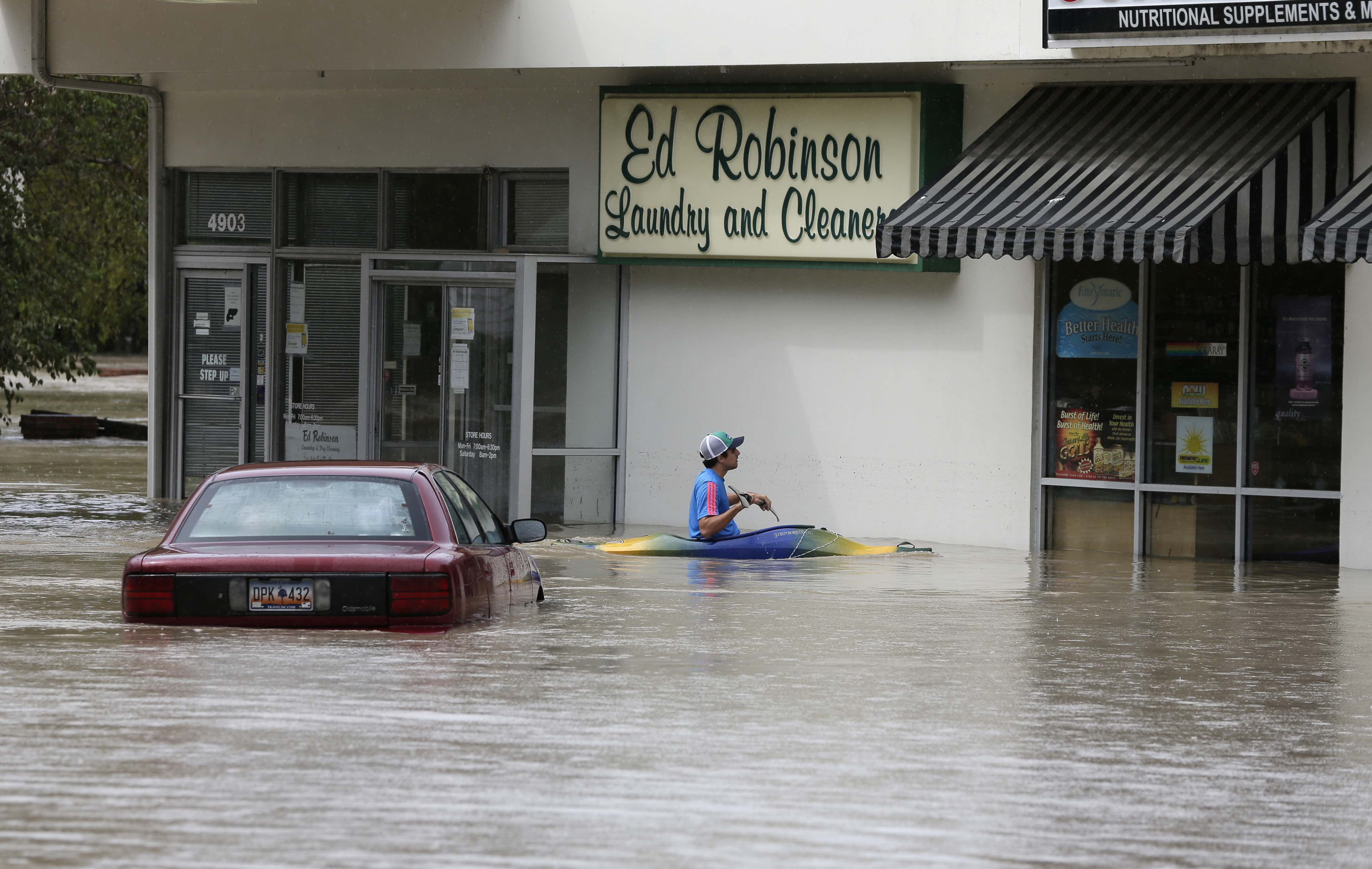 Jordan Bennett, of Rock Hill, S.C., paddles up to a flooded store in Columbia, S.C., Sunday, Oct. 4, 2015.