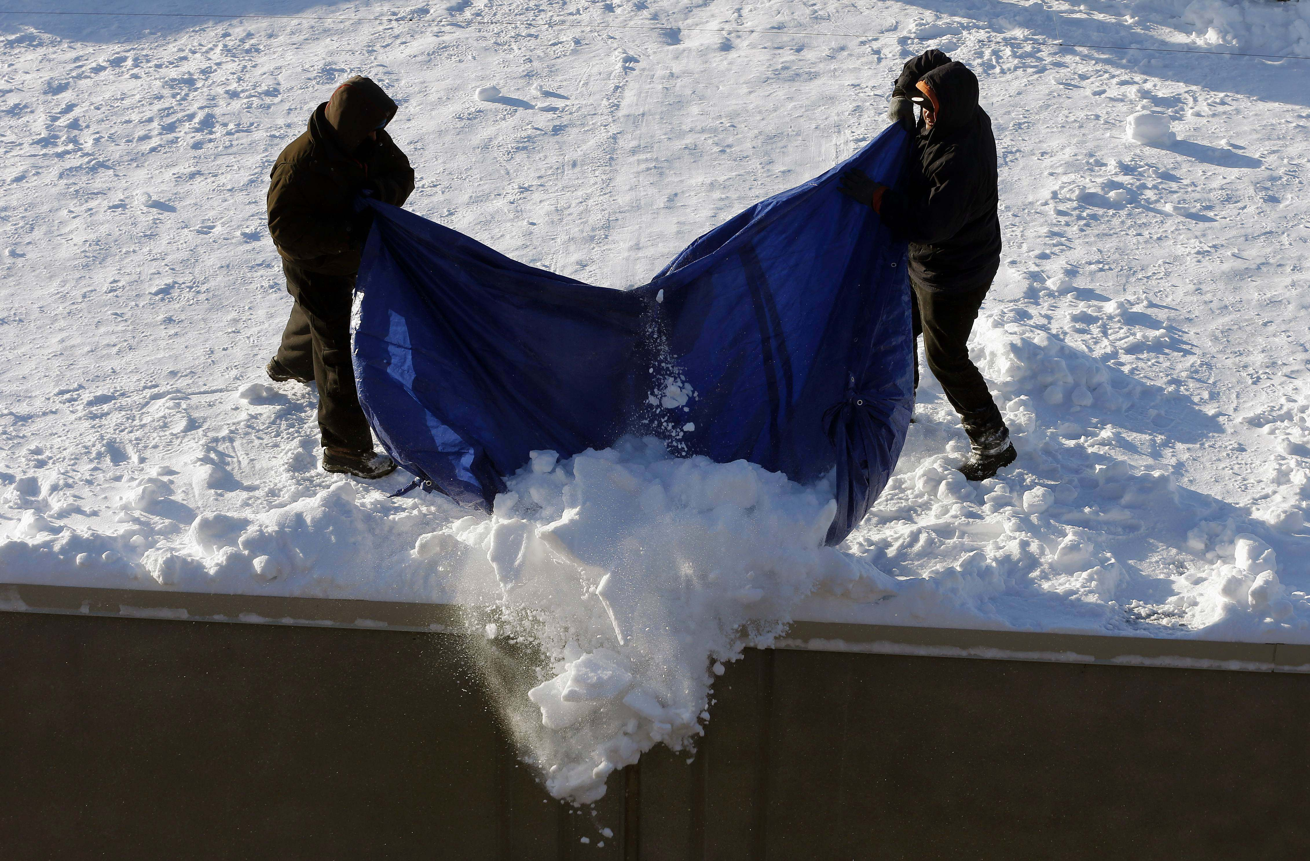 Workers clear snow from a roof in Boston, Monday, Feb. 16, 2015.
