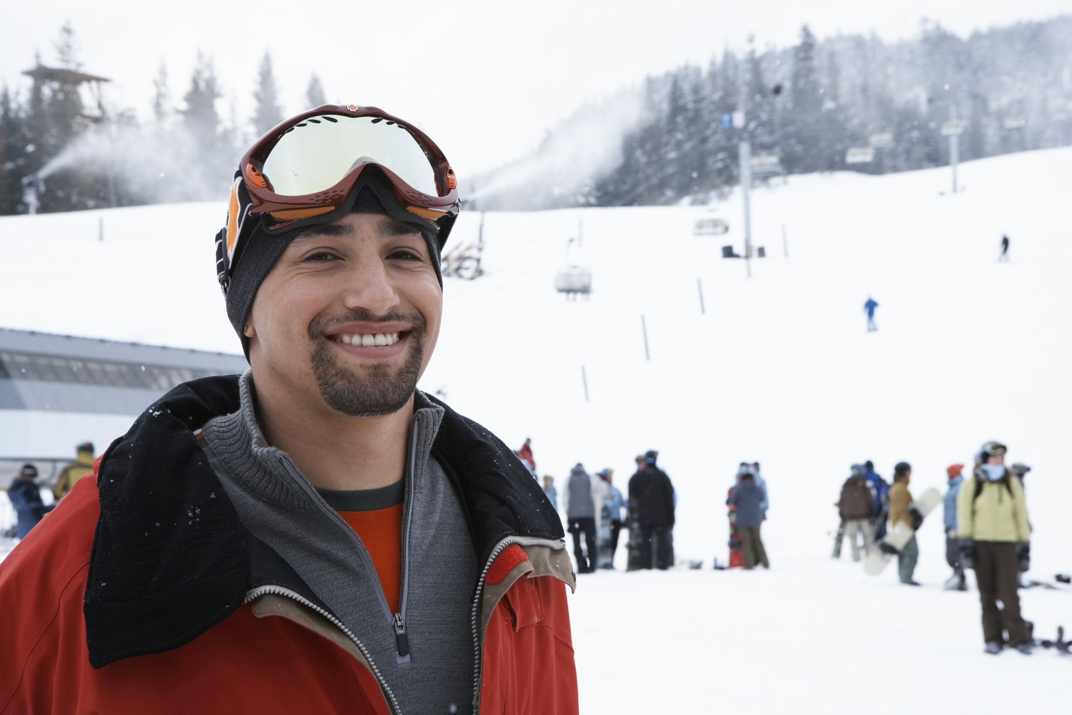 Man standing near ski lift at base of mountain with layered clothing