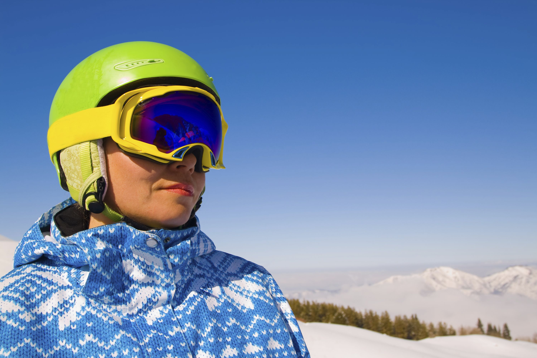 female skier wearing a green helmet and googles