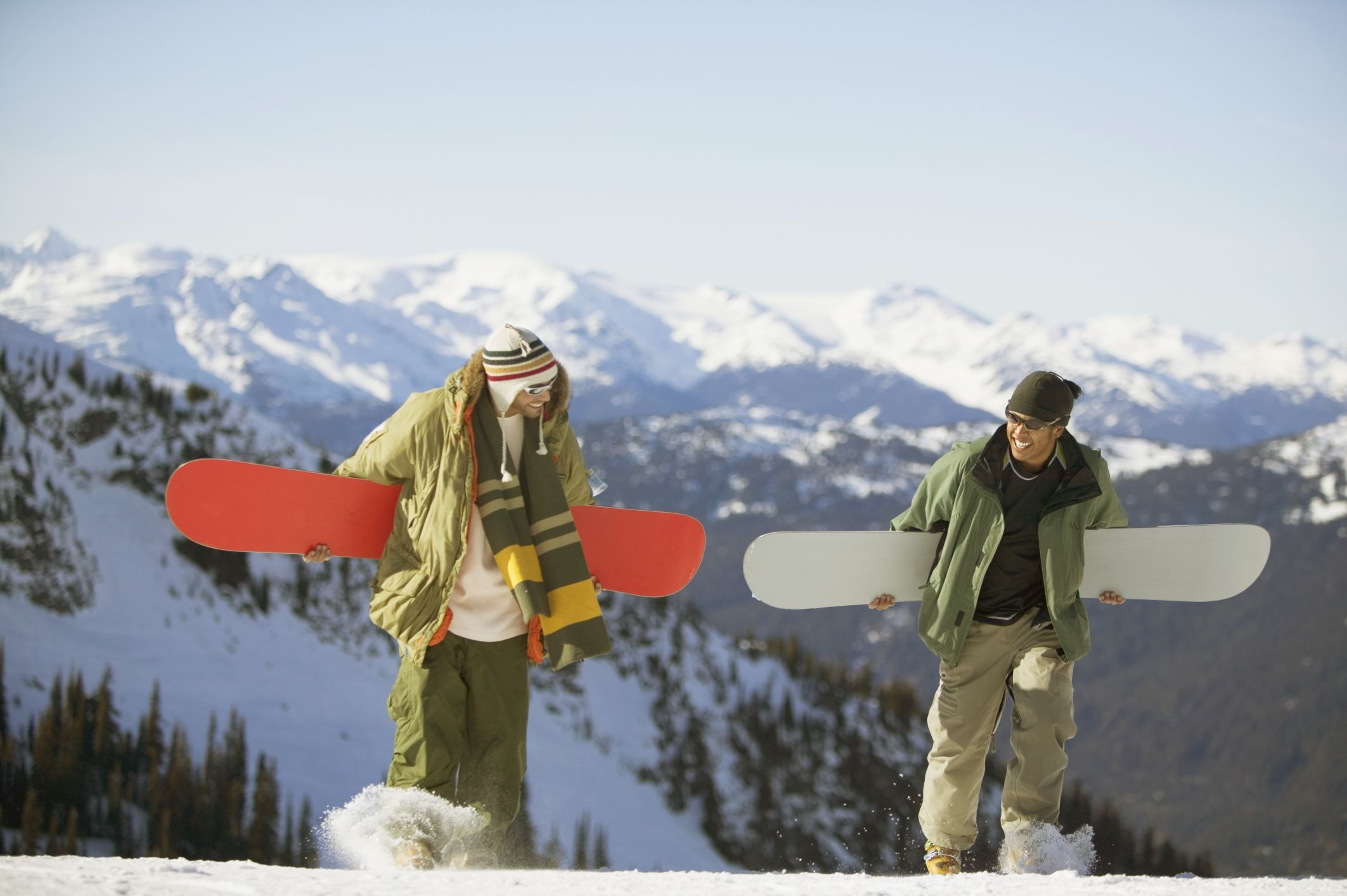 2 snowboarders carrying their boards