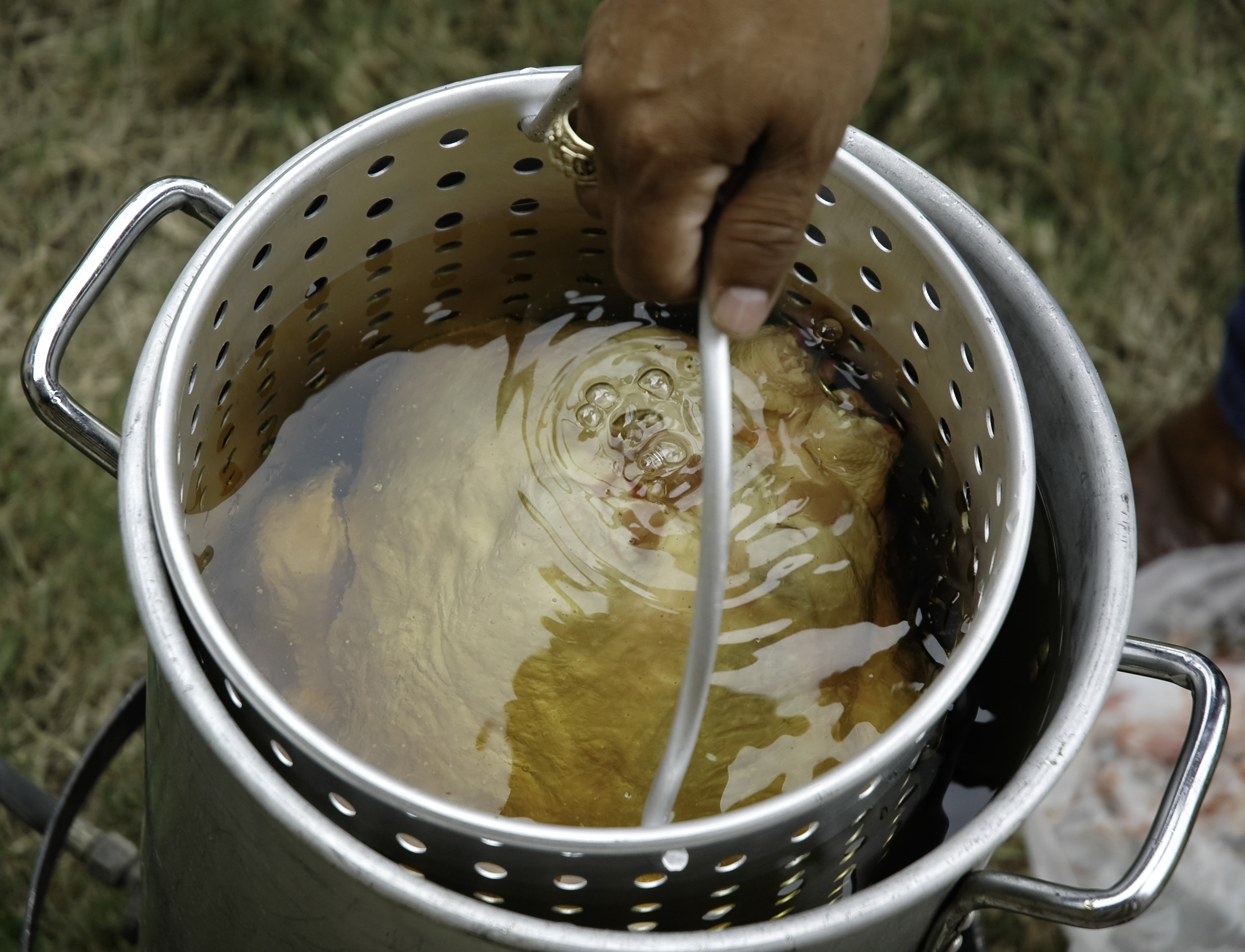 Man's-hand-dunking-turkey-in-deep-fryer-outside-crop-ThinkstockPhotos-144808200-Gustavo Perales