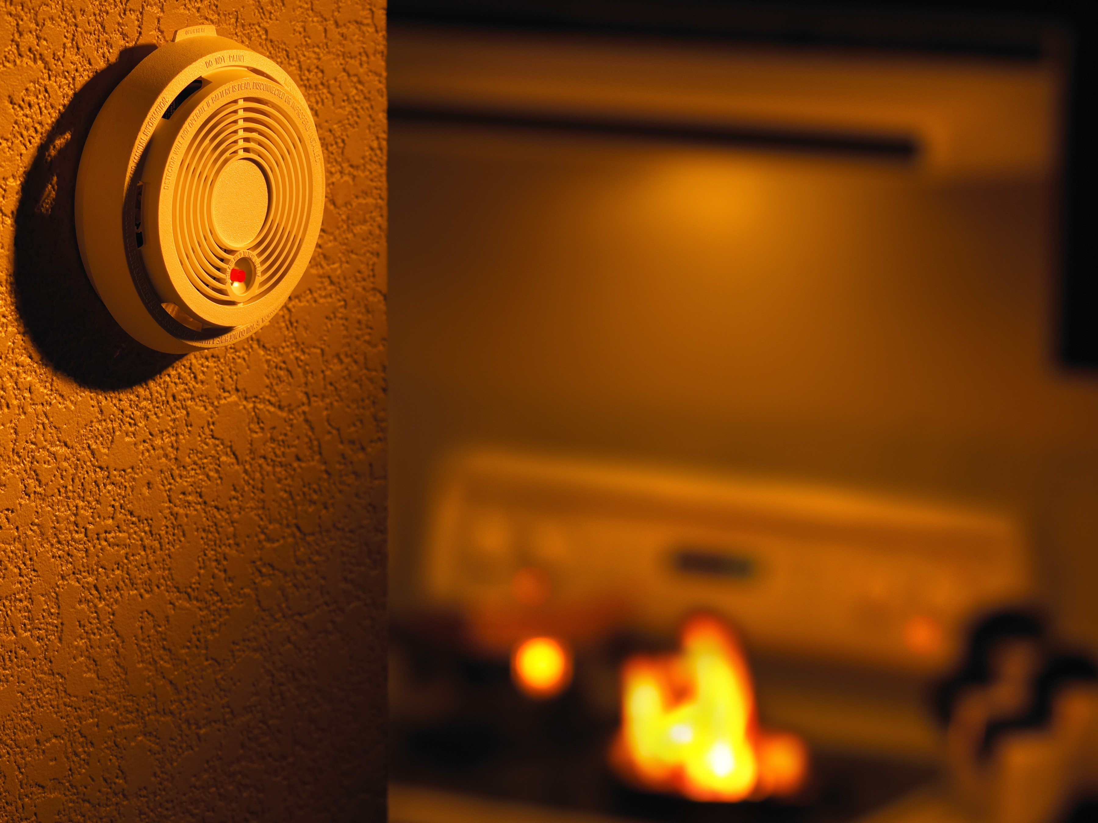 Off-centered view of smoke detector with small kitchen fire in background-ThinkstockPhotos-87630099-Jupiterimages