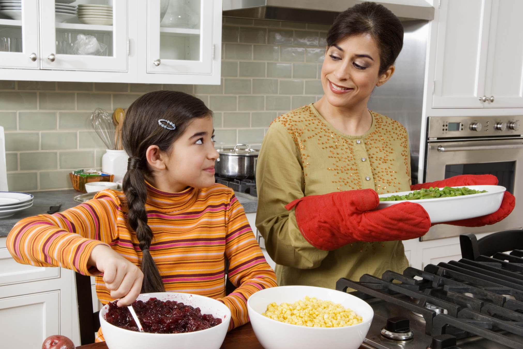 Woman-cooking-with-daughter-holding-pan-with-oven-mitts-crop-ThinkstockPhotos-76766403-Creatas Images