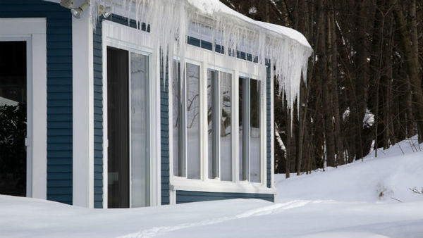 Ice dams form on roofs as snow melts and refreezes, preventing proper drainage and leading to leaks that damage interiors. (Photo: Thinkstock)