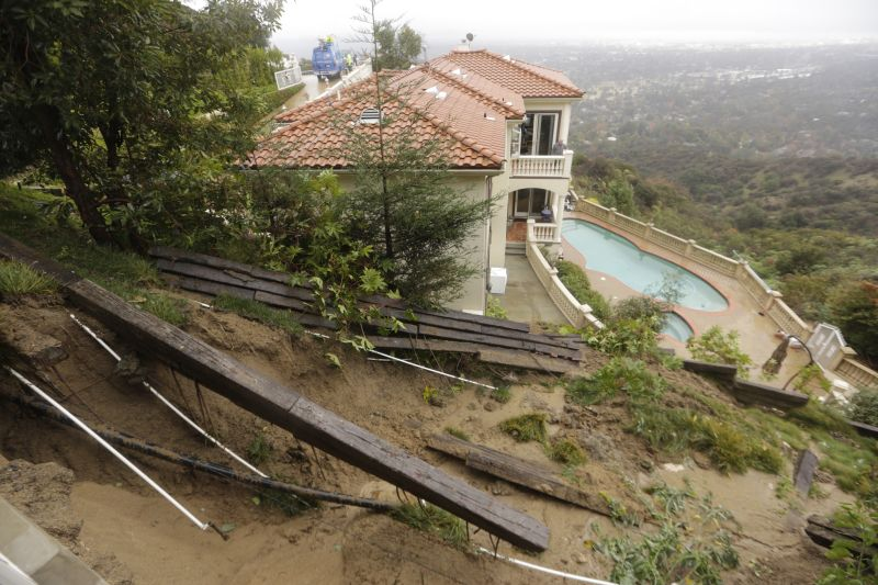 A home that was red-tagged due to debris flow breaking through its retaining wall is seen above a lower neighbor's property overlooking Pasadena, Calif., on Wednesday, Jan. 6, 2016.