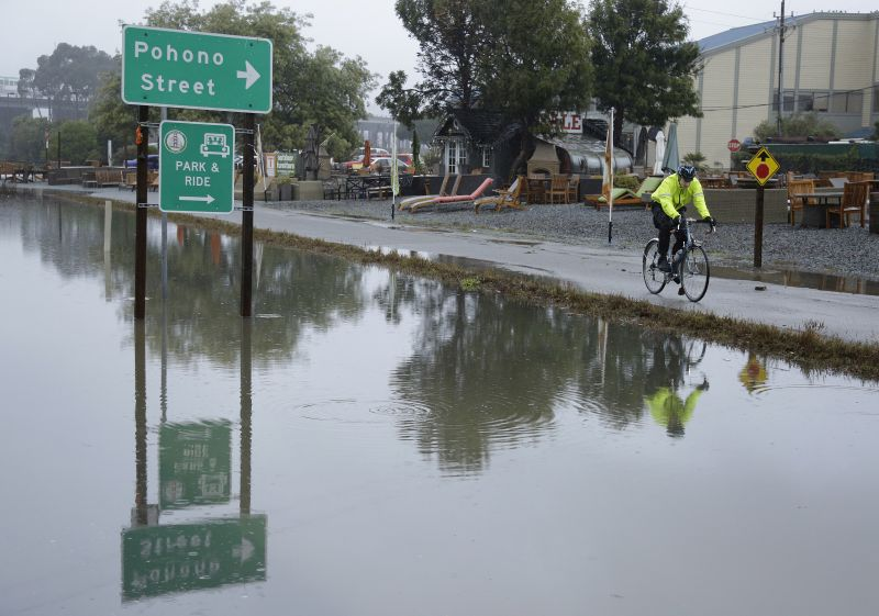 A man rides his bike past a flooded roadway Tuesday, Jan. 5, 2016, in Mill Valley, Calif.