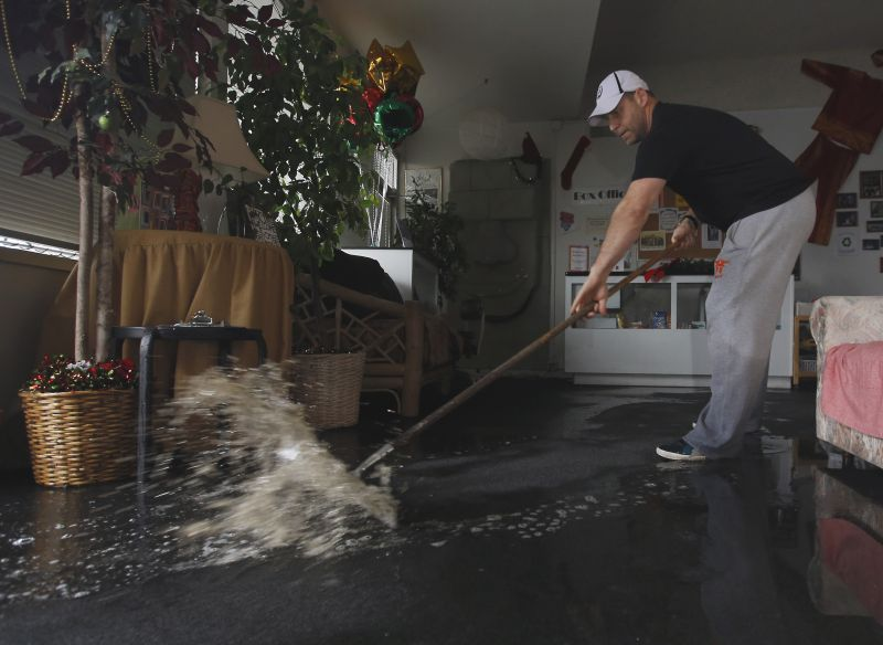 Chris Lene sweeps water out of one of the businesses in the building he owns that was flooded by rain water Tuesday, Jan. 5, 2016, in Sacramento, Calif.
