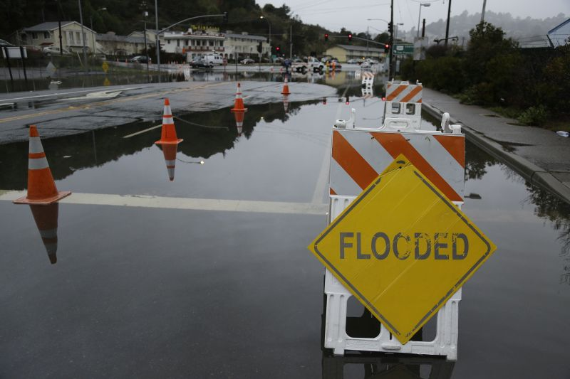 Traffic goes around a flooded roadway from high tides and rain Tuesday, Jan. 5, 2016, in Mill Valley, Calif.