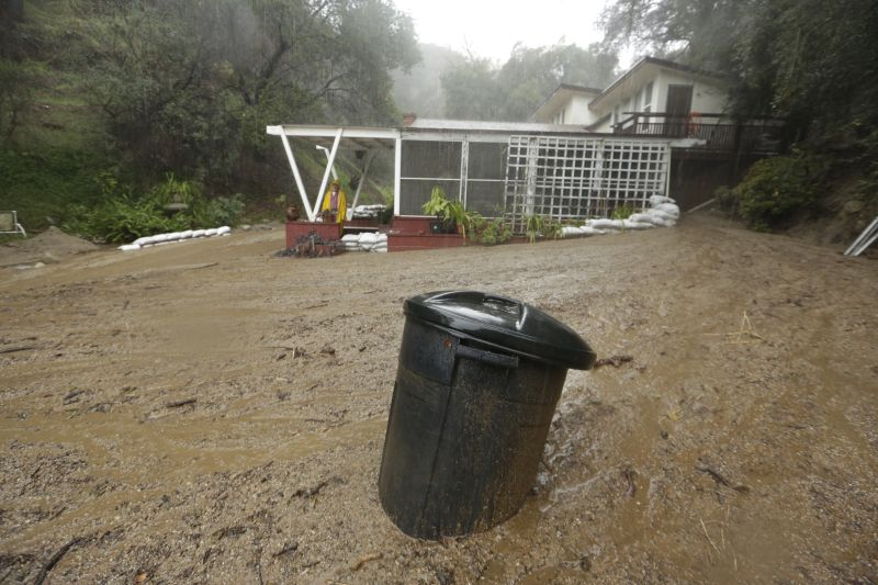 Ken Berhmann stands on his porch as storm flooding and mudslides flow through his property in Monrovia, Calif., Wednesday, Jan. 6, 2016.