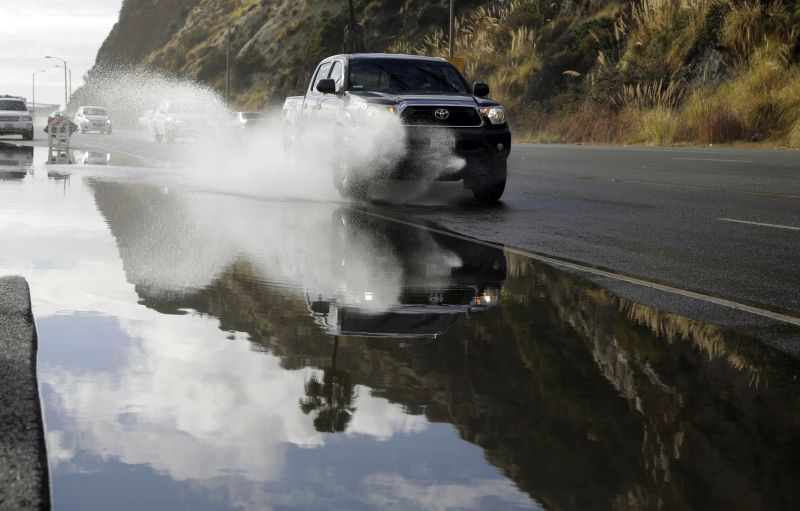 A pickup truck makes is way down a flooded road along the Pacific Coat Highway in Malibu, Calif. after a heavy rain on Tuesday, Jan. 5, 2016.