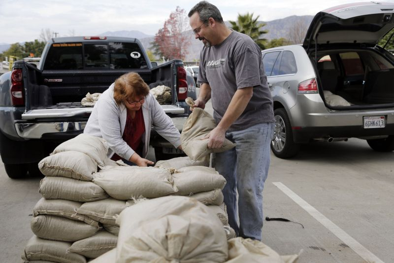 Residents Trina Gonzalez, left, and Todd Peterson stockpile sandbags to protect their homes from the rain in Glendora, Calif., Monday, Jan. 4, 2016.