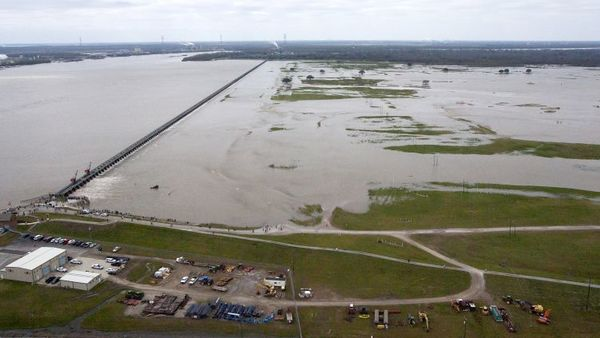 Workers with the U.S. Army Corps of engineers drain water from the Mississippi River, left, into the Bonnet Carre Spillway Sunday, Jan. 10, 2016, in Norco. The Mississippi River water levels are rising because of heavy December rain in the Midwest. The opening of the Bonnet Carre Spillway helps relieve pressure on New Orleans-area levees by making sure the water doesn't flow faster than 1.25 million cubic feet per second through the city. (Scott Threlkeld/The Advocate via AP, Pool)
