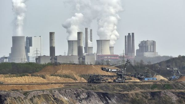 Giant machines dig for brown coal at the open-cast mining Garzweiler in front of a smoking power plant near the city of Grevenbroich in western Germany.  (AP Photo/Martin Meissner, File)