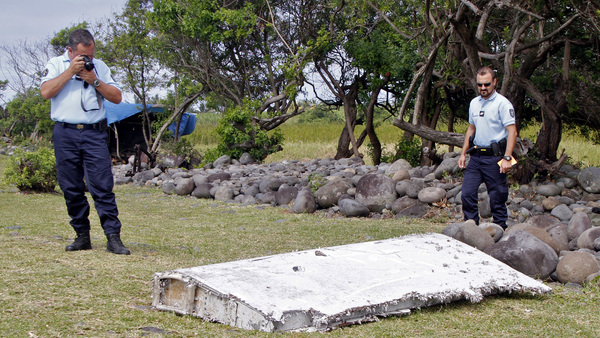 French police officers look over a piece of debris from a plane in Saint-Andre, Reunion Island. The wing was later found to be from missing Malaysia Airlines Flight 370 that went missing March 8, 2014, with 239 people aboard while flying from Kuala Lumpur to Beijing. (Photo: Lucas Marie/AP Photo)