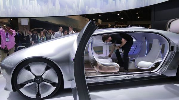 A worker rotates the seats in the self-driving Mercedes-Benz F 015 concept car at the Mercedes-Benz booth at the International CES Tuesday, Jan. 6, 2015, in Las Vegas. (AP Photo/Jae C. Hong)