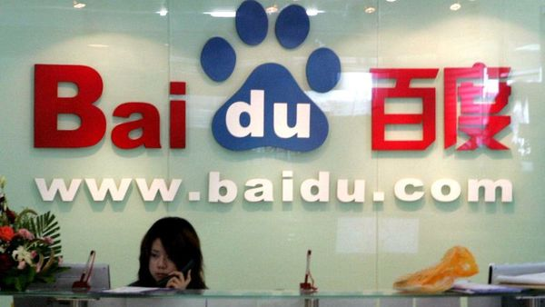 In this July 28, 2005 file photo, a receptionist works behind the logo for Baidu.com, a Chinese language search engine, at the company's office in Beijing.  (AP Photo/Ng Han Guan, File)