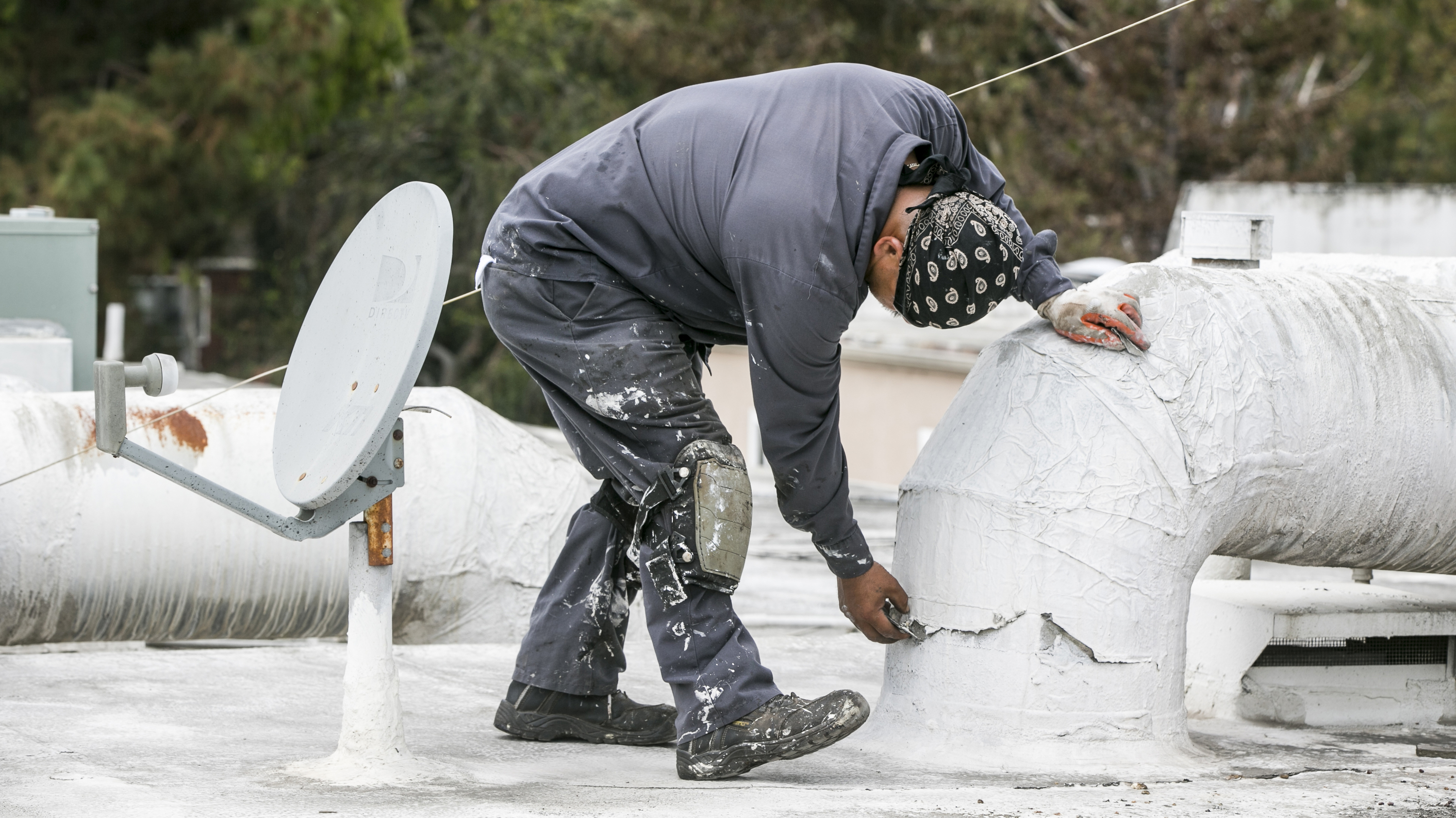 Roofer-inspecting-waterproofing-on-AC-duct-Calif_ElNino-crop-AP_809772792925-DamianDovarganes