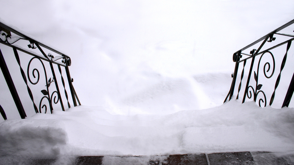 Snow-covered-steps-looking-down-with-handrail-Shutterstock