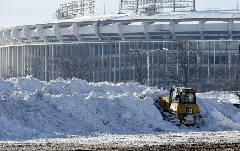 A vehicle pushes up pikes of snow after trucks dump their loads of snow in the parking lots of RFK Stadium in Washington, Monday, Jan. 25, 2016