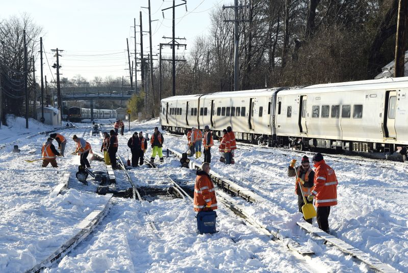 Workers clear the tracks of snow at the Port Washington branch of the Long Island Railroad, Monday, Jan. 25, 2016