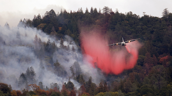 In this Sept. 15, 2015, file photo, a firefighting plane drops a load of fire retardant over a smoldering hillside in Middletown, Calif. (Photo: Elaine Thompson/AP Photo)