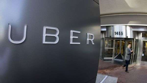 In this Dec. 16, 2014, file photo a man leaves the headquarters of Uber in San Francisco. (AP Photo/Eric Risberg, File)
