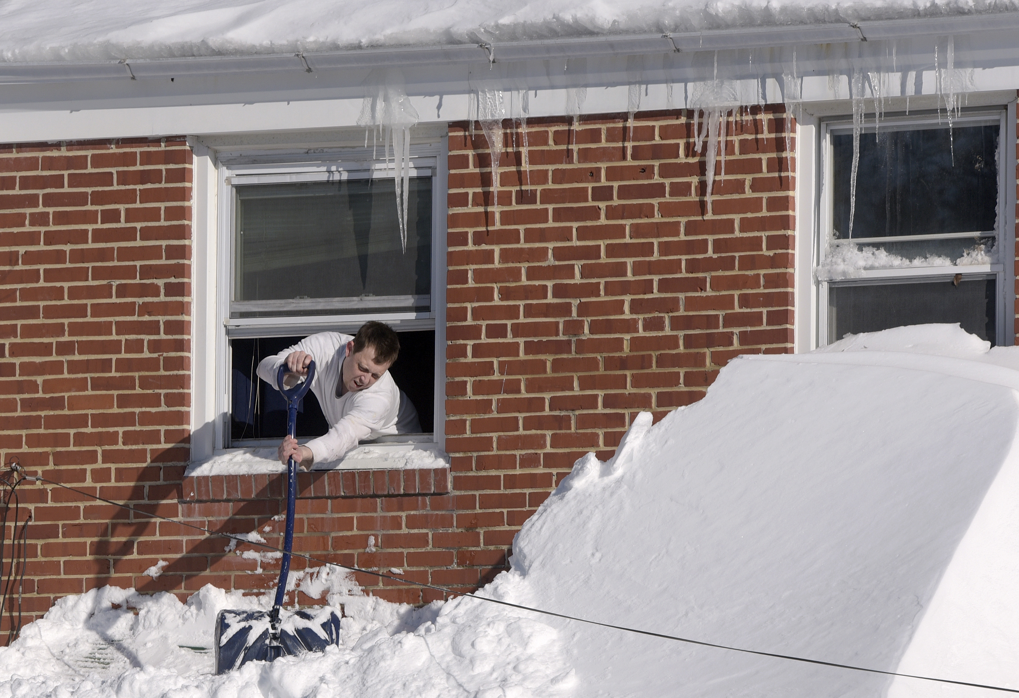 Man-clearing-snow-off-house-awning-from-second-floor-window-Blizzard-Jan-2016-crop-AP_197529660047-Steve Ruark