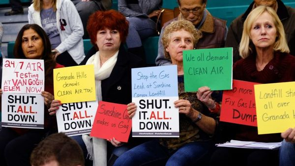 Residents hold signs during a hearing over a gas leak at the Southern California Gas Company's Aliso Canyon Storage Facility near Porter Ranch, in Los Angeles on Saturday, Jan. 16, 2016. Southern California air regulators face a simple decision Saturday over a 12-week-old gas leak that has plagued Los Angeles residents and driven thousands from their homes. (AP Photo/Richard Vogel)
