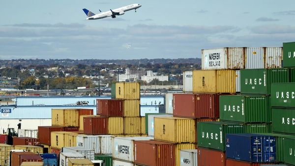 In a photo taken Friday, Oct. 30, 2015, a plane departing from Newark Liberty International Airport lifts behind a stack of containers at the Port Newark Container Terminal in Newark, N.J.  (AP Photo/Julio Cortez)