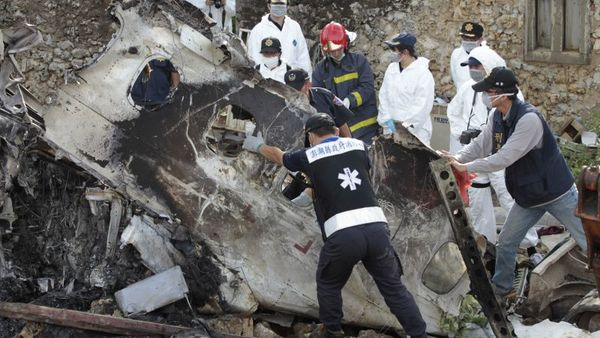 A forensic team recovers human remains among the wreckage of crashed TransAsia Airways flight GE222 on the outlying island of Penghu, Taiwan, Thursday, July 24, 2014. (AP Photo/Wally Santana)