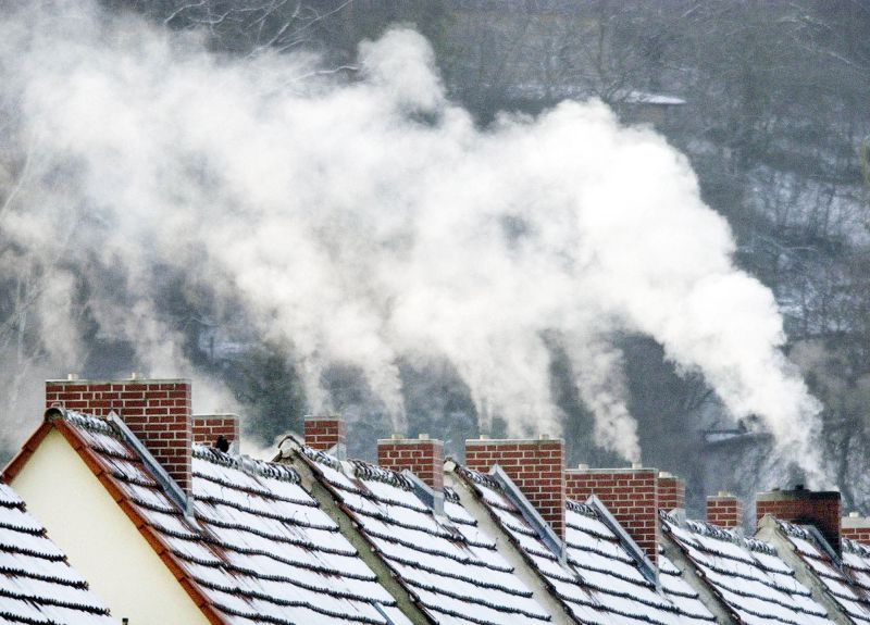Smoke slowly billows from the chimney stacks on houses