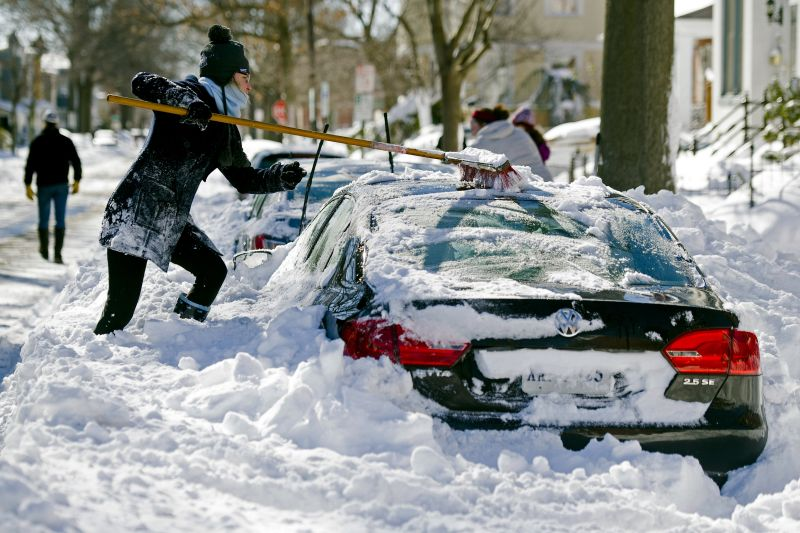 Rhianna McCarte, 30, clears snow from her car, before digging it out, in Alexandria, Va., Sunday, Jan. 24, 2016.