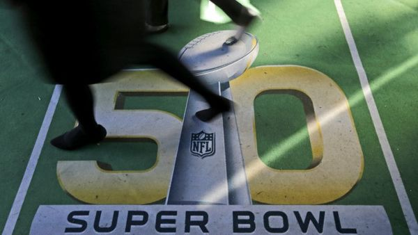 People walk across a Super Bowl 50 logo as they attend an attraction at Super Bowl City Tuesday, Feb. 2, 2016, in San Francisco. The Denver Broncos play the Carolina Panthers in the NFL Super Bowl 50 football game Sunday, Feb. 7, in Santa Clara, Calif. (Photo: Charlie Riedel/AP Photo)