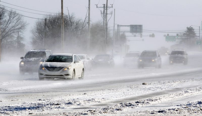 Motorists drive their cars through blowing snow Sunday, Feb. 15, 2015, in Yardley, Pa.