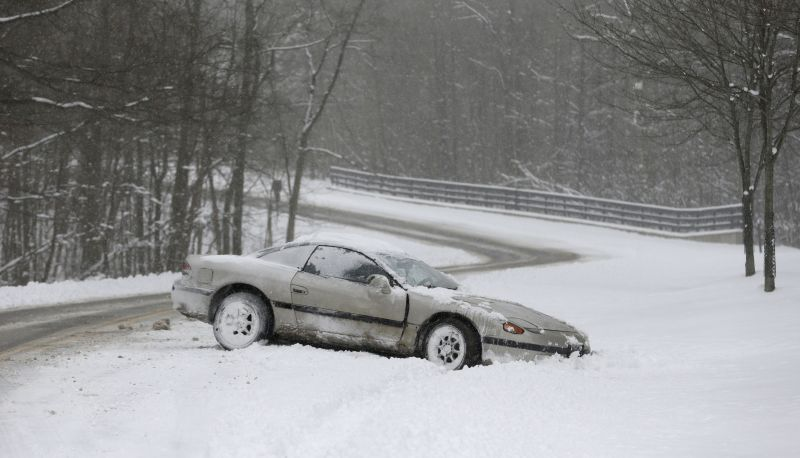 A car rests on the side of the road in the snow Friday, Feb. 1, 2013, in Solon, Ohio.