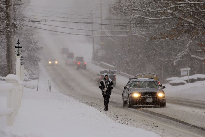 Traffic is sparse and the sidewalks impassable as a heavy snow falls in Pembroke, Mass.