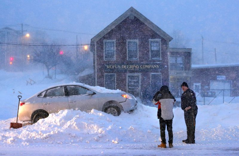 A police officer questions the driver an occupant of a car that ended up on top of a tall snowbank in the middle of Commercial Street during a blizzard in Portland, Maine.
