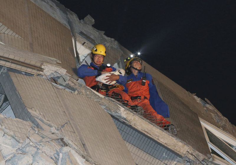 Rescue workers carry a baby swaddled in a cloth from the rubble of a toppled building after an earthquake in Tainan, Taiwan