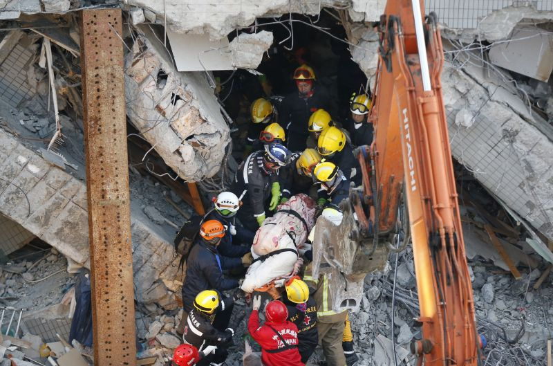 Emergency rescuers remove a body found in a collapsed building