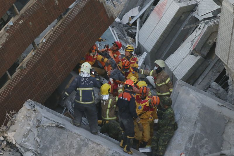 Rescue workers carry a 28-year-old Vietnamese woman, identified as Chen Mei-jih, rescued from the rubble of a collapsed building complex