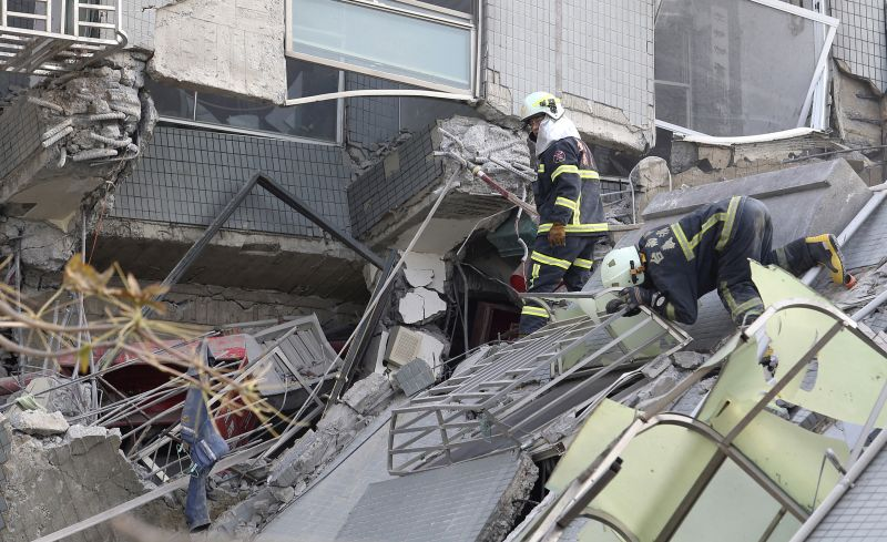 Emergency rescue teams search for victims in a collapsed building