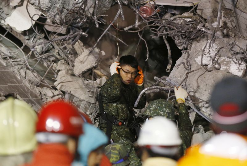 An army soldier tries to listen for signs of life in a collapsed building