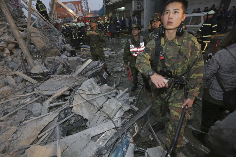 Army soldiers search a toppled building an earthquake in Tainan, Taiwan, Saturday, Feb. 6, 2016.