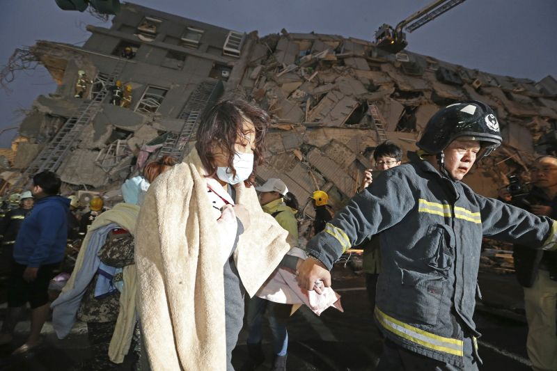 A woman is led by a rescue worker from the site of a toppled building