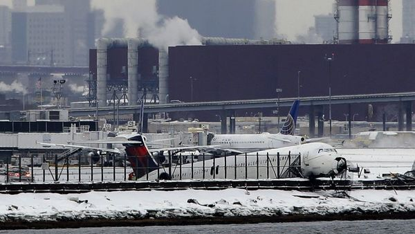 A plane that skidded off the runway at LaGuardia Airport hangs over the edge of the runway in New York, Thursday, March 5, 2015. The plane, from Atlanta, skidded off the runway while landing, and crashed through a chain-link fence. (AP Photo/Seth Wenig, File)