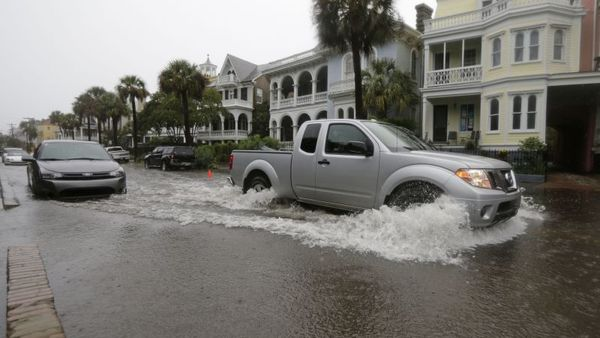 A car drives through a flooded street in Charleston, S.C., Saturday, Oct. 3, 2015. A flash flood warning was in effect in parts of South Carolina, where authorities shut down the Charleston peninsula to motorists. (AP Photo/Chuck Burton)